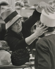 Ruth-Marion Baruch  -  Hat Woman Pressing Hat on Customer, 1961 / Silver Gelatin Print  -  11 x 14