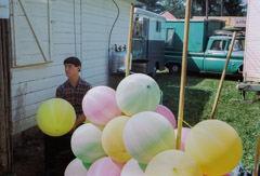Vivian Maier  -  Location unknown, 1966, (Young man and balloons) / Chromogenic Print  -  10 x 15 on 16 x20 paper