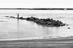 Tim Barnwell  -  2335, Fisherman, rocks, near Ft. Moultire with Ft. Sumter behind, Charleston, SC /   -