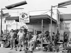 Thomas Neff  -  Mr. Joe Peters and Crew, St. Claude Used Tires, St. Claude Avenue, Ninth Ward, September 20, 2005 / Silver Gelatin Print  -  20 x 24