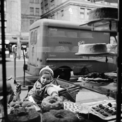 Vivian Maier  -  1954, New York NY (bakery window) / Silver Gelatin Print  -  12 x 12 (on 16x20 paper)